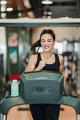 Happy sportswoman exercising on treadmill in gym - p300m2265293 by Eva Blanco