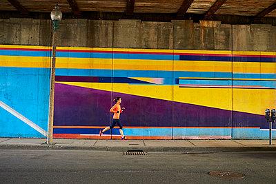 Woman running past underpass mural in Boston, Massachusetts, USA - p343m1500291 by Josh Campbell