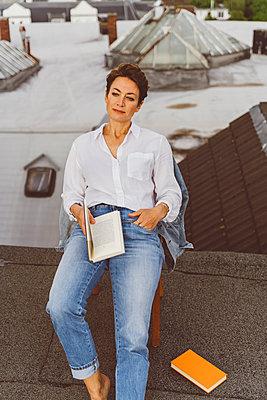 Fraut sitzt entspannt mit Buch auf Dach - p432m2185650 von mia takahara