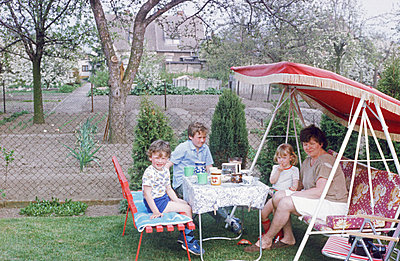Germany, Family drinking coffee in the Hollywood swing in the GDR - p986m2223985 by Friedrich Kayser