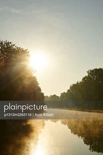 River and forest in the backlight with sun and haze - p1312m2263116 by Axel Killian