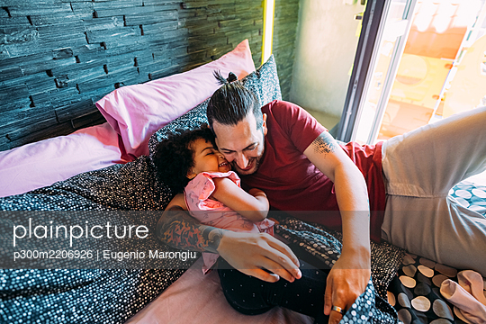 Playful father and daughter lying on bed at home - p300m2206926 by Eugenio Marongiu