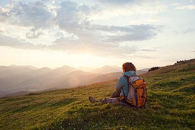 Austria, Tyrol, Unterberghorn, hiker resting in alpine landscape at sunrise - p300m1059140f by Rainer Berg