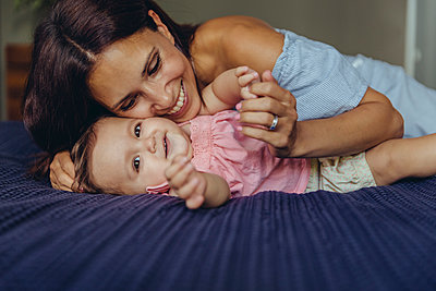 Happy mother cuddling with her baby girl on bed - p300m2042747 by Mareen Fischinger