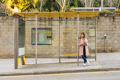 Young woman with cell phone waiting at bus stop - p300m2083064 von VITTA GALLERY