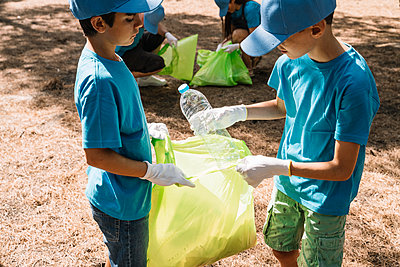Group of volunteering children collecting garbage in a park - p300m2131923 by Jose Luis CARRASCOSA