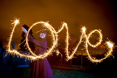 Woman writing LOVE with sparkler - p42918443f by Leon Harris