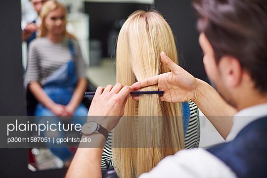 Rear view of hairdresser combing woman's hair - p300m1587051 von gpointstudio