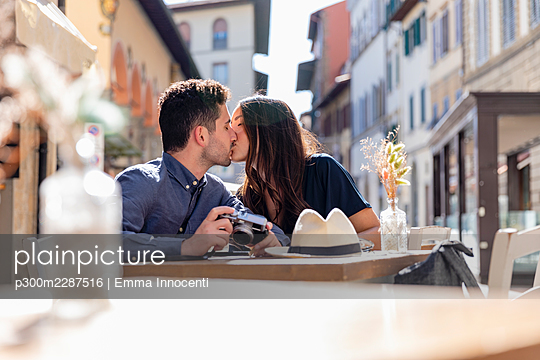 Tourist couple kissing each other at sidewalk cafe - p300m2287516 by Emma Innocenti