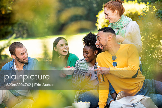 Happy young friends having picnic in public park - p623m2294742 by Eric Audras