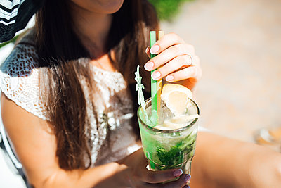 girl is a drink fruit alcohol cocktail based on lime, mint, oran - p1166m2094712 by Cavan Images