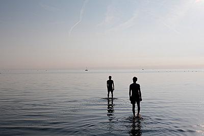 Junge Männer stehen im Badesee - p1212m1178657 von harry + lidy