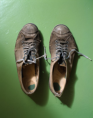 Old worn out shoes on floor - p1614m2185787 by James Godman