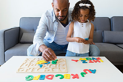 Father and daughter playing with alphabet learning game at home - p300m2114565 von Sus Pons