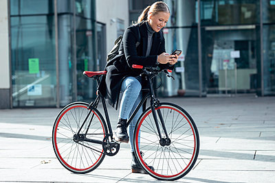 Smiling woman using mobile phone while leaning on bicycle - p300m2256035 by Josep Suria