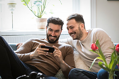 Smiling young men looking at smart phone while sitting on sofa at home - p426m1588699 by Maskot