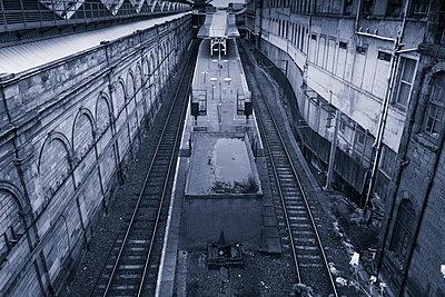 Old disused railway platform tracks empty blue - p609m1219851 by OSKARQ