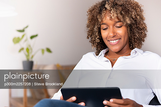 Mid adult woman smiling while using digital tablet sitting at home - p300m2257208 by Steve Brookland