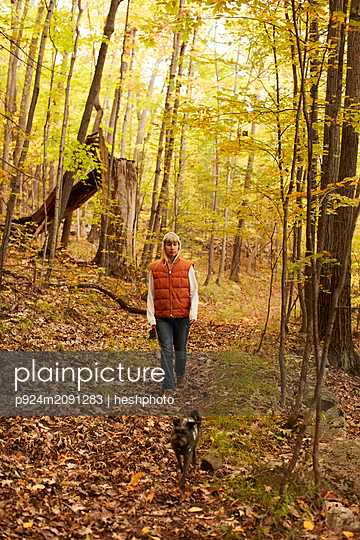 Woman walking dog in woods - p924m2091283 by heshphoto