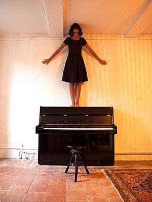 Woman standing on piano - p1105m2128783 by Virginie Plauchut