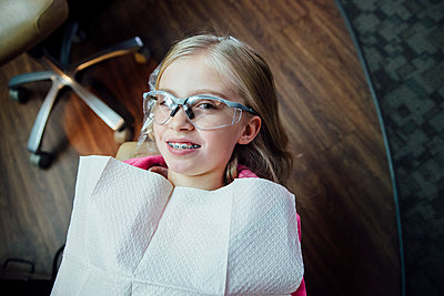High angle portrait of girl with braces sitting at dentists office - p1166m1518970 by Cavan Images
