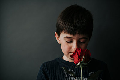Close-up of boy with eyes closed smelling rose while standing against wall - p1166m2001051 by Cavan Images