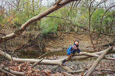 Boy with backpack sitting on fallen tree in forest - p1166m2001185 by Cavan Images
