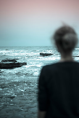 Blurry female figure looking out onto a rough sea - p1433m2127054 by Wolf Kettler