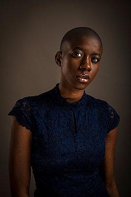 Studio portrait of a bald black women facing camera - p1619m2199936 by Laurent MOULAGER