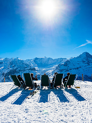 Switzerland, Canton of Bern, Grindelwald, view from First to Wetterhorn and Eiger, skiers sitting on deckchairs in the sun - p300m1224511 by Martin Moxter