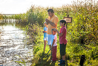 Father and children standing at water course, Darss, Mecklenburg-Western Pomerania, Germany - p300m2143736 by Ega Birk