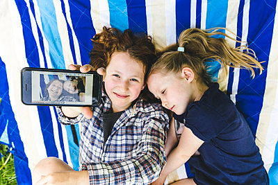 Girl showing photograph on smart phone while lying by sister on picnic blanket - p300m2202708 by Irina Heß