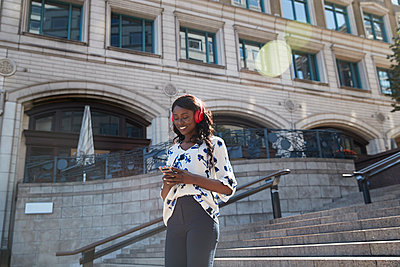 Smiling businesswoman listening music while walking on staircase in city - p300m2241630 by Pete Muller