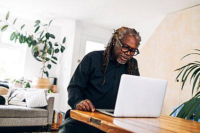 Senior businessman working on laptop at table - p300m2293311 by Angel Santana Garcia
