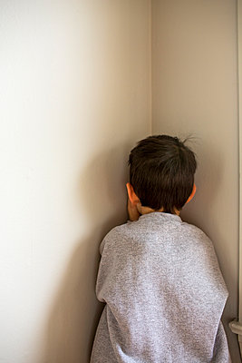 Mixed Race boy standing in corner - p555m1482108 by Adam Hester