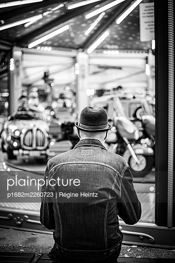 Man sitting in front of a carousel - p1682m2260723 by Régine Heintz