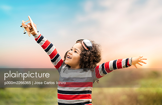 Happy cute boy playing with wooden toy airplane in nature during sunset - p300m2266365 by Jose Carlos Ichiro