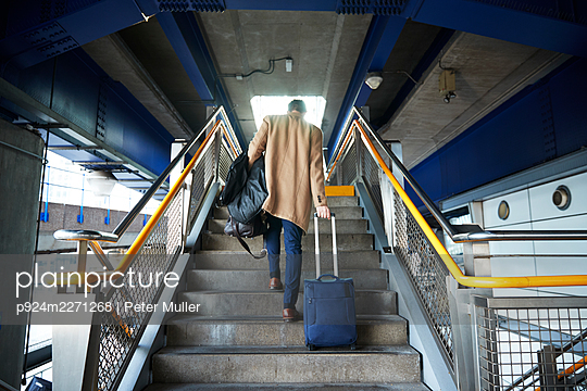 UK, London, Man with luggage walking up steps - p924m2271268 by Peter Muller
