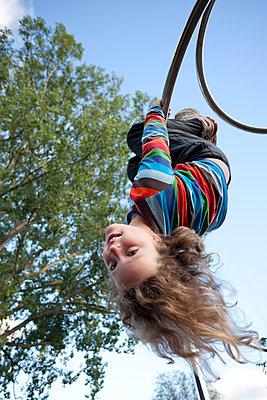Girl on a playground upside down - p1687m2284299 by Katja Kircher
