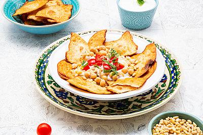 Fatteh (levantinisches Gericht, Frühstück oder Zwischenmalzeit, Mezze) geröstetes, in Stücke zerbrochenes Fladenbrot, Minz-Joghurt, Kichererbsen, Olivenöl, Tomate und Tahin - p300m2144336 von Larissa Veronesi