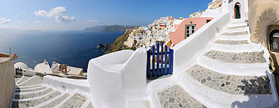 View of Oia village with cobbled path and blue gate at Santorini - p300m731268f by Martin Rügner