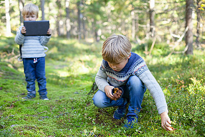 Toddler taking photograph of brother picking up wild mushrooms in forest - p429m2145505 by Tiina & Geir