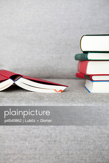 Stack of books on a sofa - p4540862 by Lubitz + Dorner