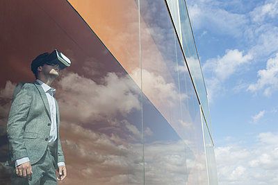 Businessman using virtual reality simulator glasses at modern window with cloud reflection - p1023m1519865 by Martin Barraud