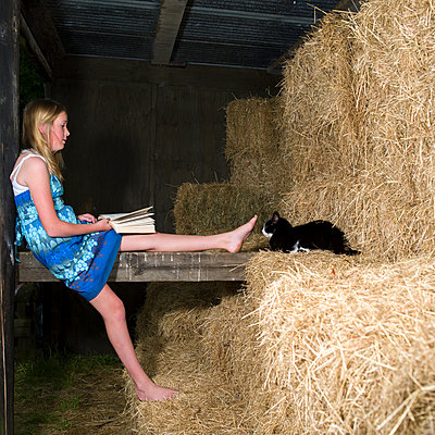 Girl on hay stake in barn - p1201m1048078 by Paul Abbitt