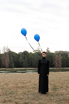 Woman in black dress with blue balloons, portrait - p1521m2214994 by Charlotte Zobel