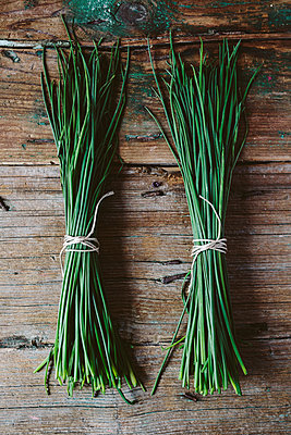 Two bunches of chives on wood - p300m1355928 by Giorgio Fochesato