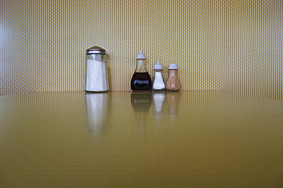 Condiments lined up on a restaurant table; London, England - p442m936960f by Ingrid Rasmussen