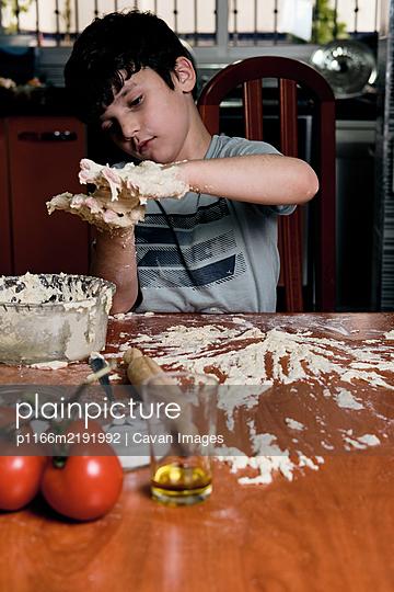 young boy prepares pizza dough at home - p1166m2191992 by Cavan Images