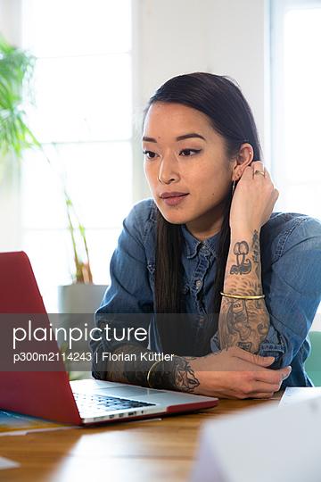 Woman using laptop at table in office - p300m2114243 von Florian Küttler